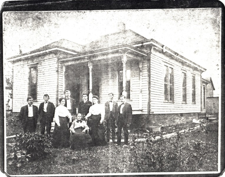 Photocopy of old photo, family standing before house